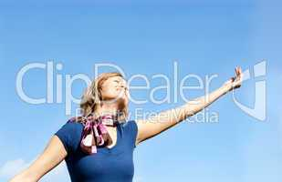 Smiling  blond woman against blue sky