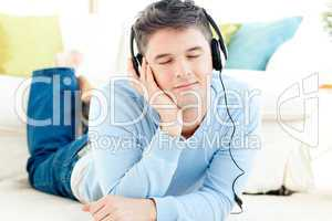 Handsome young man listening music lying on the floor