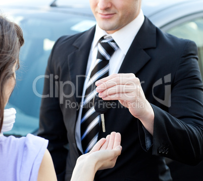 Close-up of a salesman giving car's key