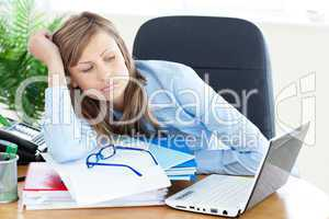 Stressed young businesswoman sitting at her desk
