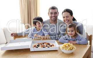 Happy young family eating a pizza in the living-room