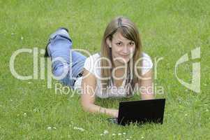 Junge Frau mit Netbook auf Wiese