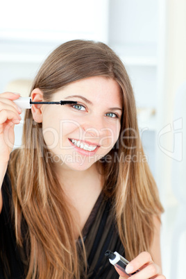 Portrait of a smiling woman put one's eye make up on