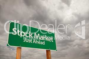 Stock Market Green Road Sign Over Storm Clouds