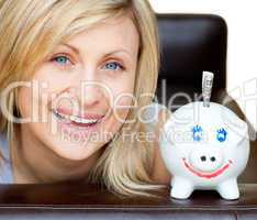 Laughing woman with a piggy bank