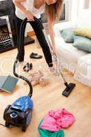 Blond young woman cleaning the living-room