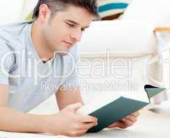Interested young man reading a book lying on the floor