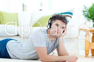 Young man with headphones lying on the floor in the living room
