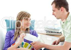 Caring man giving his ill girlfriend tissue lying on a sofa