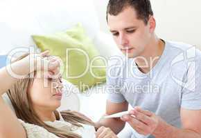 Caring man check the temperature of his sick girlfriend with a t