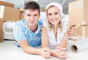 Jolly couple lying between boxes