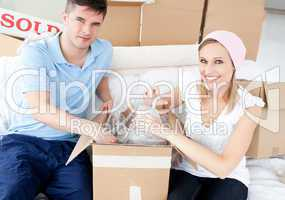 Smiling young couple unpacking boxes with glasses