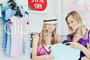 Cute young women choosing clothes together