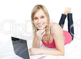 Modern woman lying with a laptop on sofa