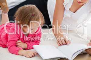 Kind mother reading a book with children