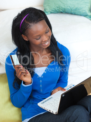 Laughing woman using a laptop sitting on bed