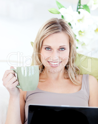 Woman sitting in front of her laptop and holding a cup