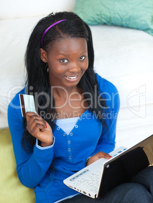 Young woman using a laptop sitting on bed