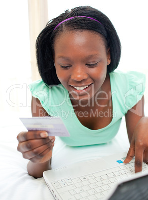 Smiling woman using a laptop sitting on bed