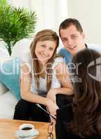 Smiling couple listen to a saleswoman siting on a sofa
