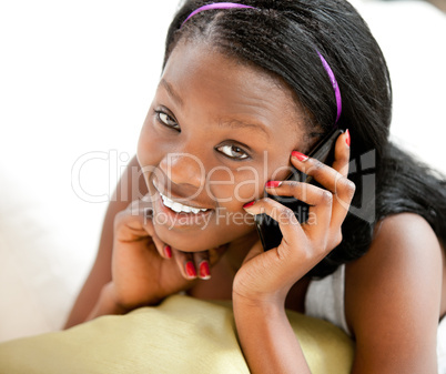 Glowing afro-american teenager talking on phone smiling at the c