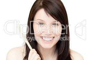 Portrait of a glowing young woman holding a nail file