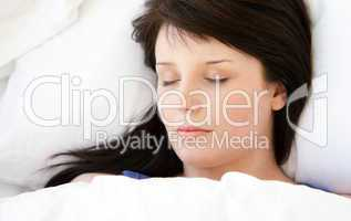 Beautiful young woman lying in a bed sleeping
