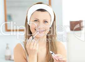 Glowing woman applying gloss on her lips wearing a headband