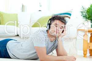 Charming young man listen to music lying on the floor