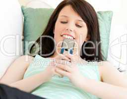 Delighted teenager sending a text message lying on the sofa