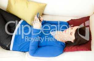 Relaxed young woman sending a text message lying on the sofa