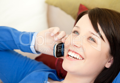 Cheerful female teenager talking on phone lying on a sofa