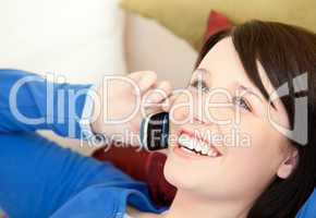 Cheerful female teenager talking on phone lying on a sofa