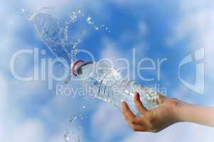 Spritzer und Tropfen aus der Mineralwasserflasche in der Hand