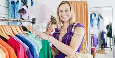 Joyful young woman choosing clothes with her friend
