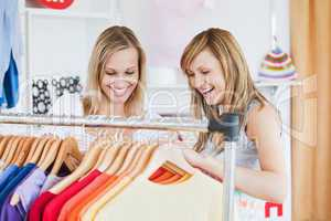 Pretty female friends doing shopping choosing shirts
