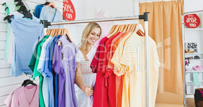 Merry blond woman choosing colorful clothes