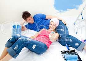 Attentive couple relaxing after paiting a room