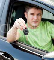 Happy young male driver sitting in blue car