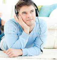 Positive man with headphones lying on the floor