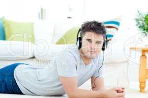 Handsome man with headphones lying on the floor