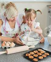 Smiling woman baking cookies with her daughters