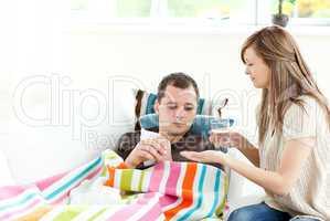 Caring girlfriend giving his sick boyfriend pill