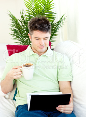 Concentrated young man using his laptop drinking coffee