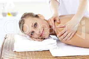 Jolly young woman receiving a back massage