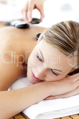 Charming young woman enjoying a back massage with hot stone