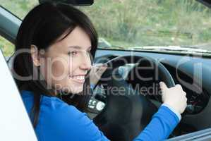 Happy female teenager sitting in her new car