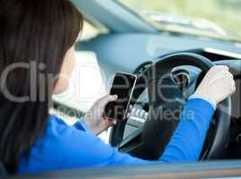 Brunette young woman using her cellphone while driving