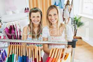 Attractive women smiling at the camera standing in a clothes sto