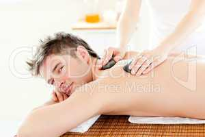 Charming young man receiving a back massage with hot stone